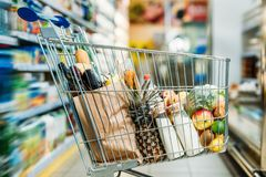 Selective focus of shopping cart with purchases. In supermarket Stock Image