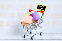 Add to cart. Selective focus of shopping cart or trolley with yellow blackboard written with & x27;ADD TO CART& x27;. Shopping theme Royalty Free Stock Photography