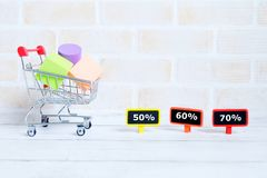 50% ,60%,70%. Selective focus of shopping cart or trolley with yellow blackboard written with & x27;50%,60%,70%& x27;. Shopping theme Royalty Free Stock Images