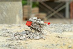Selective focus on shopping trolley carries the crushed stones and pouring onto the pile at the construction site royalty free stock photo