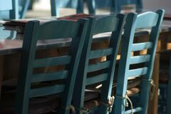 Selective focus shot of blue chairs next to a table in an old taverna in Folegandros, Greece