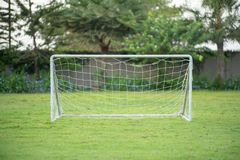 Selective focus on a small soccer goal with rope net puts on the grass field with blurred garden and trees in background royalty free stock photography