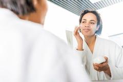 Selective focus of smiling african american woman. Applying face cream near mirror in bathroom stock photos