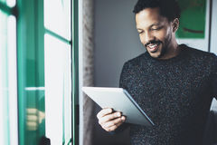 Selective focus.Smiling bearded African man reading book on digital tablet while standing near the window in his modern. Apartment.Concept of young business Royalty Free Stock Photography