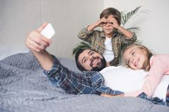 selective focus of smiling father and kids taking selfie on smartphone together stock image
