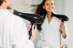 Selective focus of smiling girl in bathrobe using hair dryer at mirror. In bathroom royalty free stock photography