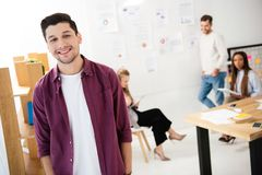 Selective focus of smiling marketing manager looking at camera with multicultural colleagues behind. In office royalty free stock photography