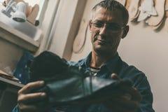 Selective focus of smiling mature cobbler in eyeglasses holding leather shoe. In workshop stock images