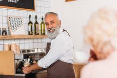 selective focus of smiling senior barista making coffee stock photo