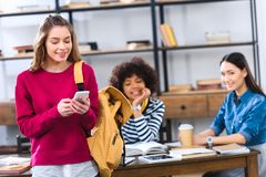 Selective focus of smiling student with smartphone and multicultural friends. Studying behind stock photo