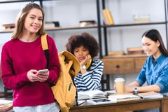 Selective focus of smiling student with smartphone and multicultural friends. Studying behind stock images