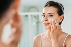 Selective focus of smiling young woman. Applying face cream and looking at mirror in bathroom royalty free stock photo