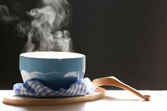 Selective focus of smoke rising with hot soup in cup and spoon o. N dark background royalty free stock photo