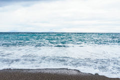 Selective focus Soft waves foam in blue ocean italy coast, summe. R evening as background Royalty Free Stock Image