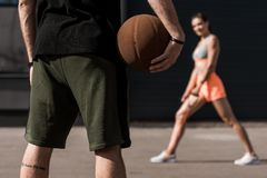 selective focus of sportsman with basketball ball and sportswoman stretching stock images