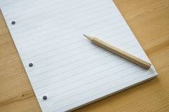 A stack of blank striped paper from a school notebook with a simple black small pencil for writing, space for text. Selective focus, a stack of blank striped stock photo