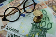 Selective focus on stacked of Euro coins with Euro banknotes and. Glasses as finance concept Stock Photos
