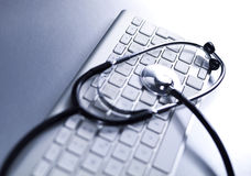 Selective focus of a stethoscope lying on a computer keyboard. Stock Photos
