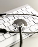 Selective focus of a stethoscope lying on a computer keyboard. Stock Images
