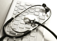Selective focus of a stethoscope lying on a computer keyboard. Royalty Free Stock Photo