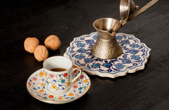 Selective focus still-life with colorful coffee cup, walnuts and oriental cezve with dark drink Royalty Free Stock Image
