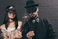 selective focus of stylish multiethnic couple in christmas masks with sparkles at new stock images