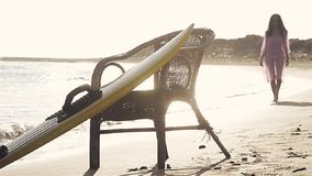 Selective focus on surf board on the beach with a walking girl defocus stock video footage