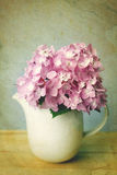 Selective focus of sweet purple hydrangea flowers in white vase royalty free stock photo
