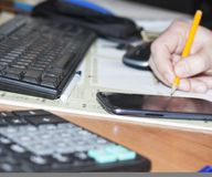 Selective focus-table: handwork, calculator, mobile phone, laptop and pen on a wooden table. Job royalty free stock images