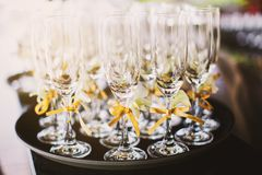 Selective focus on a tall wine glasses decorated with gold ribbon on the tray with light from the back royalty free stock photo