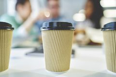 Mock up copy space coffee to go cup for logo. Selective focus on three disposable cardboard cups with coffee beverage made of recycling material standing on Royalty Free Stock Photo