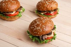 Selective focus of three musackgroundhroom burgers with raw ingredients, wooden b royalty free stock photos