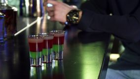 Selective focus on three shots on the bar table man using his smart phone on the background. Selective focus on alcohol colorful shots cocktails on the bar table stock video footage