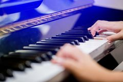Selective focus to fingers of woman teaching boy to play the piano. royalty free stock photos