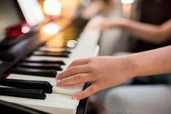 Selective focus to kid`s hand playing piano on stage stock photo