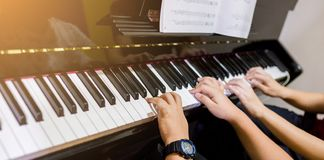 Selective focus to picture of young woman teaching a boy to play the piano with music notation royalty free stock image