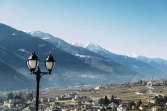Selective focus of traditional lamppost and dining set table overlooking Sondrio, an Italian town and comune located in the heart. Selective focus of traditional royalty free stock photos