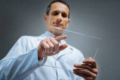 Selective focus on transparent gadget held by mature man. Innovative ideas. Low angle shot of a mature man wearing a white coat focusing his attention on a Stock Image