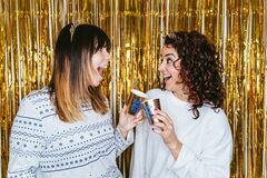 Selective focus. Two brunette women in pajamas having fun together on New Year`s Eve and holding two cups wishing a Happy New Yea