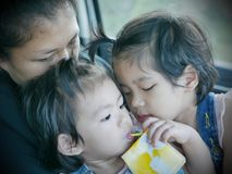 Two little Asian baby girls, siblings, cuddling on her mother`s lap in a car during a trip royalty free stock images