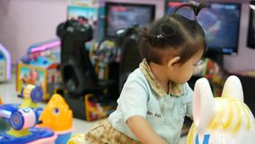 Selective focus of two little Asian baby girls, sisters, enjoys taking a ride on motorbike arcade game, coin operated.  stock footage