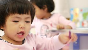 Selective focus of two little Asian baby girls siters, sitting on a desk, holding crayons and painting at home. Selective focus of two little Asian baby girls, 3 stock footage