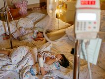Two sick Asian baby girls, siblings, were together admitted and staying in a hospital. Selective focus of two sick Asian baby girls, siblings, were together royalty free stock image