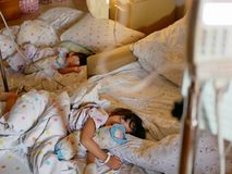 Two sick Asian baby girls, siblings, were together admitted and staying in a hospital. Selective focus of two sick Asian baby girls, siblings, were together royalty free stock images