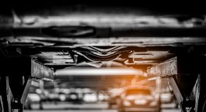 Selective focus on underneath a lifted car in garage workshop. Auto service business. Automotive parts concept. Car parked in car. Service shop. Car check up stock image