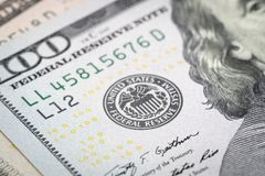 Selective focus on US Federal Reserve emblem on hundred dollars. Banknote as FED consider interest rate hike, economics and inflation control national stock images