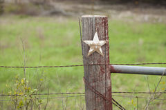 Selective focus view of grungy star on old fence post in Texas. A selective focus view of a grungy white star on a wooden fence post in Texas Royalty Free Stock Photo