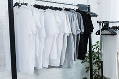 selective focus of white black and grey empty t-shirts on hangers in clothing design royalty free stock photos