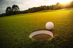 Selective focus. white golf ball near hole on green grass good f. Or background with sunlight and lens flare effect Royalty Free Stock Photo