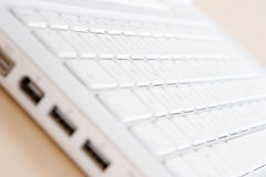 Selective focus on a white keyboard. A close up shot of a white laptop keyboard with empty slots at the front Royalty Free Stock Photo